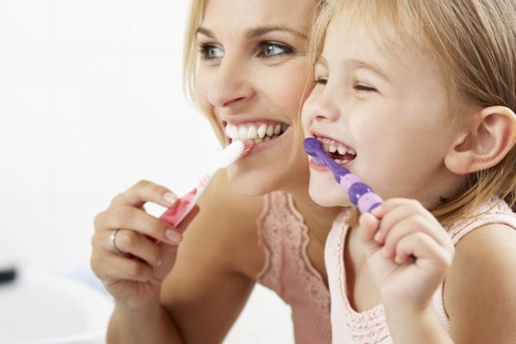 smile forever mother and daughter brushing teeth